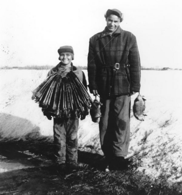 Two people stand with hunting paraphernalia
