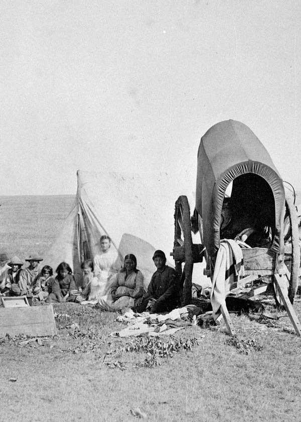 A Metis family camps by their two-wheeled Red River cart