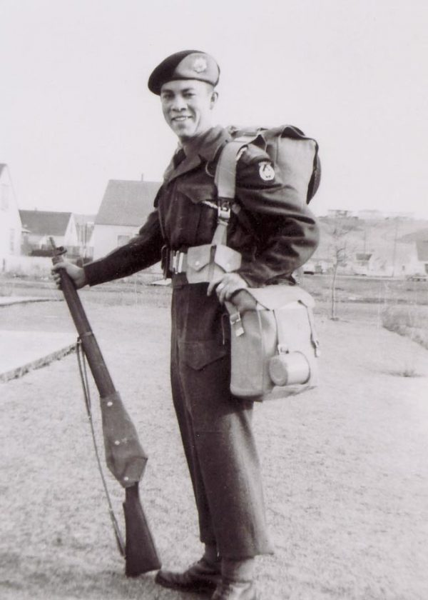 A man wearing a military uniform poses with a rifle