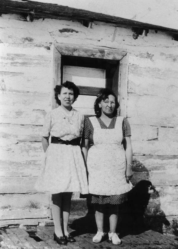 Two women stand in front of a house