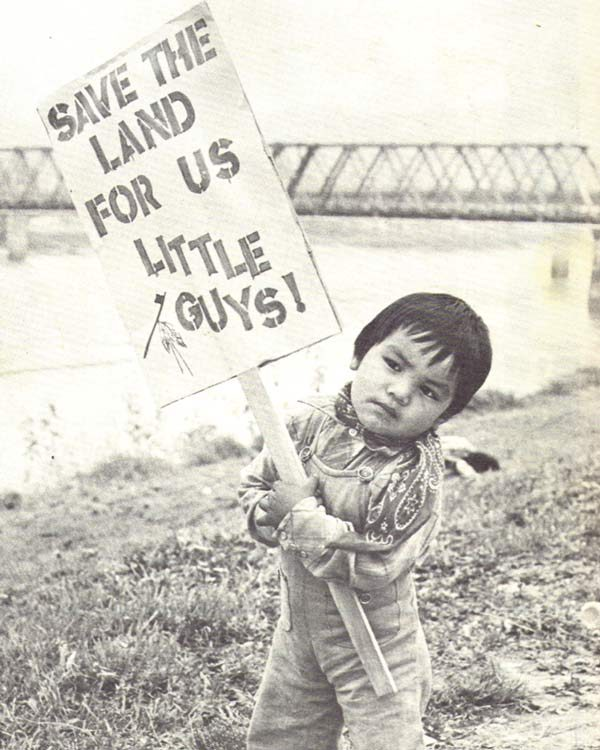 A small child holds up a sign saying