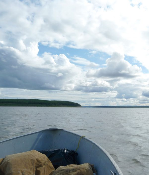 Boat on water in foreground with a cloudy, blue sky in the background