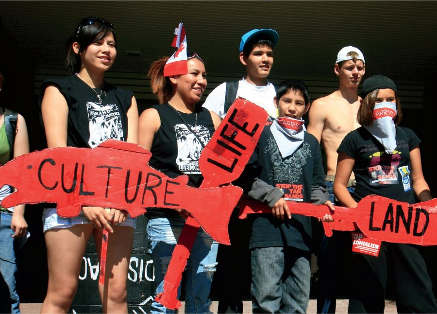 Teens holding red signs reading