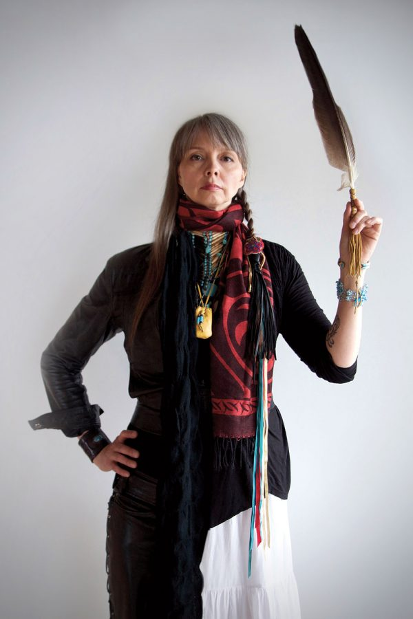 Woman standing with one hand on hip and other holding a large feather