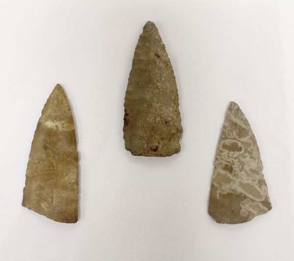 Three old looking arrow heads on a white surface