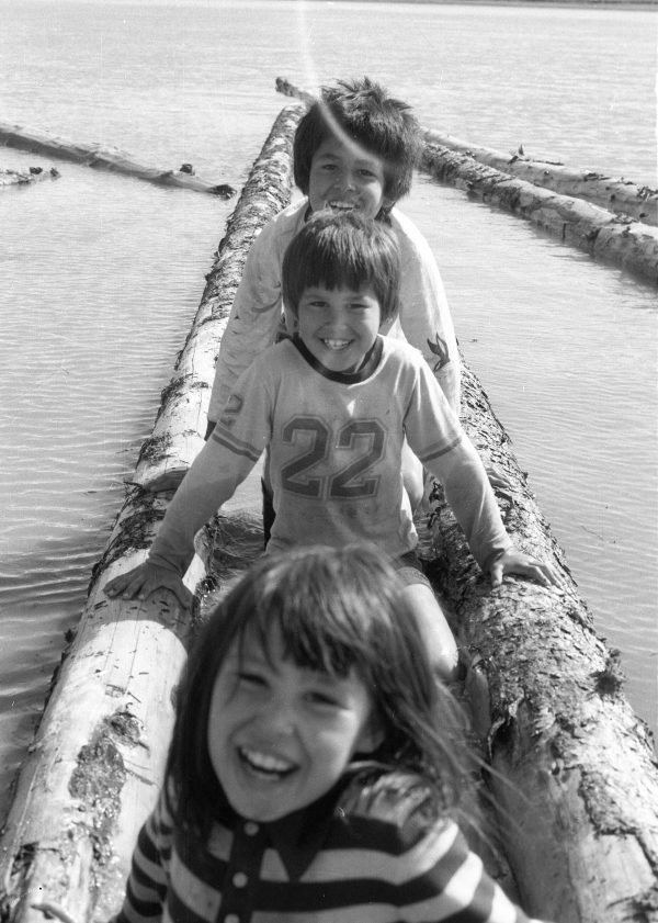 Black and white - three kids playing with driftwood on water